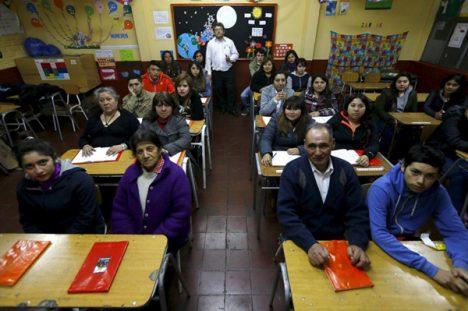 سانتیاگو، شیلی. گیلرمد والنزوئلا در کنار دانشآموزان ابتدایی شبانهی بزرگسالان در مدرسهی لورا ویکونا عكس: Ivan Alvarado